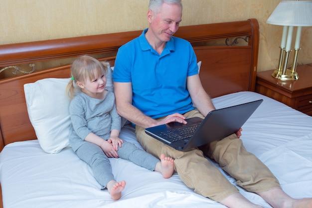 Отец и дочь, лежа на кровати и используя ноутбук дома,