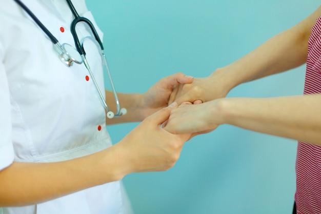 励ましと共感のために患者さんの手を握っている女性医師の手。