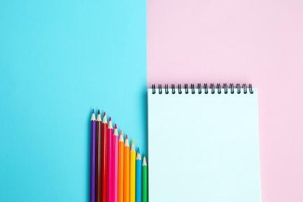 Цветные карандаши и блокнот на цветной стене.