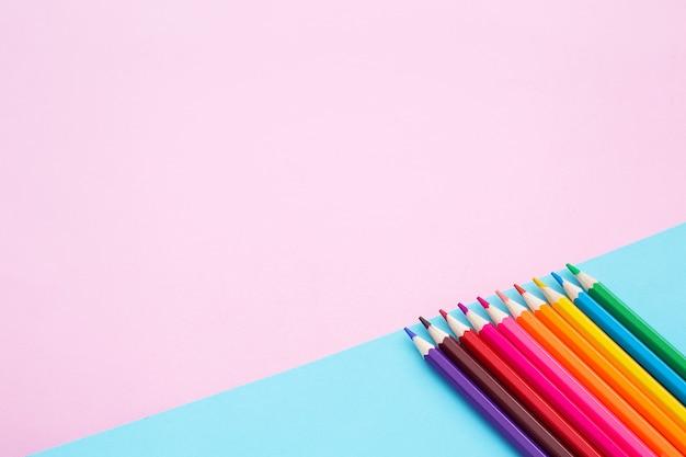 Цветные карандаши на голубой и розовой стене.