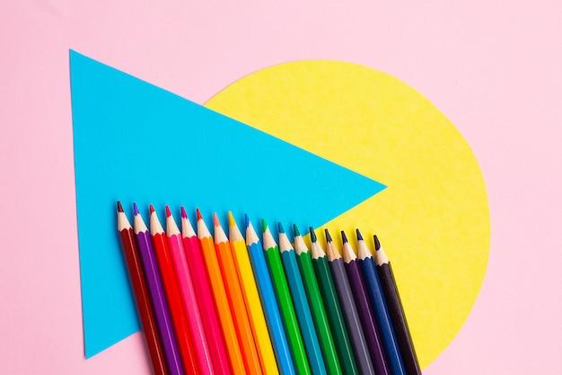 Цветные карандаши и геометрические фигуры на цветной стене.