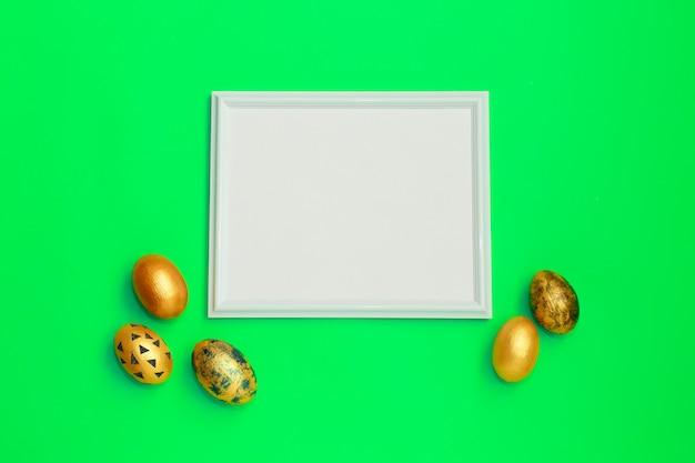 緑色の背景上のテキストのコピースペースとゴールドのまだらイースターエッグのあるフレーム。