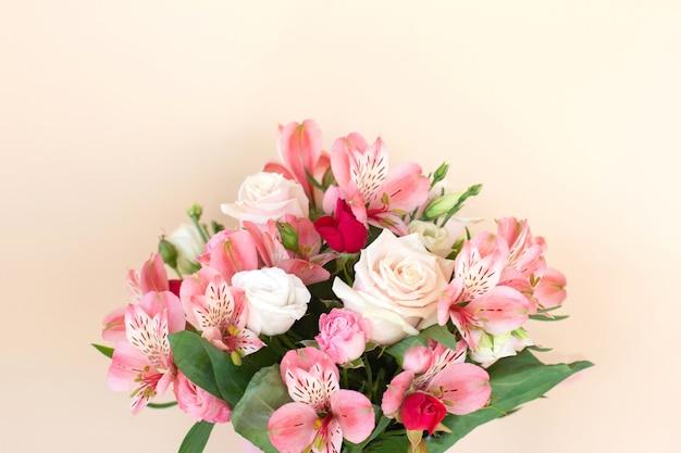 明るい背景にバラとアルストロメリアの花の美しい花束。