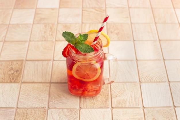 新鮮なイチゴのカクテル。冷たいイチゴのレモネード、レモンと氷、木製のテーブルのメイソンジャー