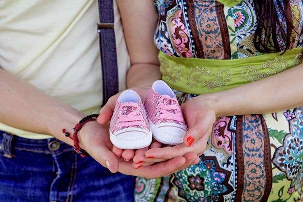 Беременная пара держит свои будущие детские ботинки