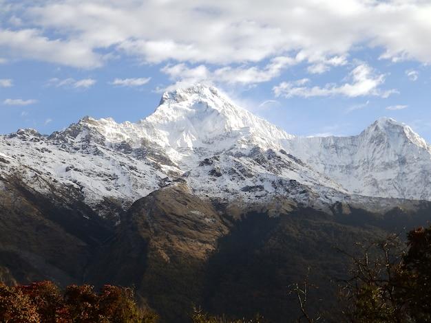 曇りの背景に雪に覆われた岩山の頂上