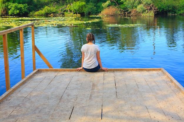 Счастливая молодая девушка сидит на пристани и смотрит на озеро