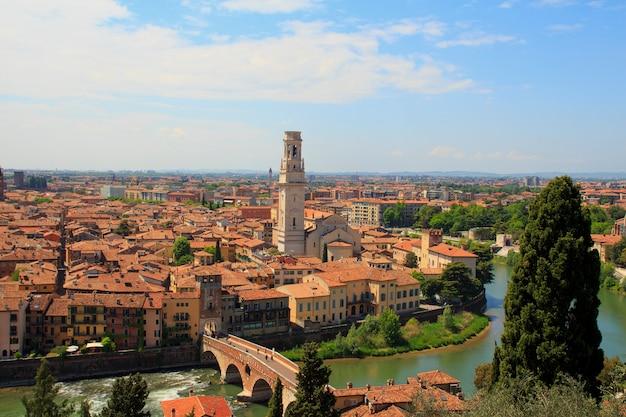 オレンジ色の屋根と晴れた日に高い塔とヴェローナ旧市街の空撮