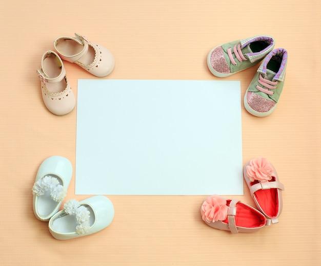 靴と生まれたばかりの女の子のための背景。子供服のコンセプトです。
