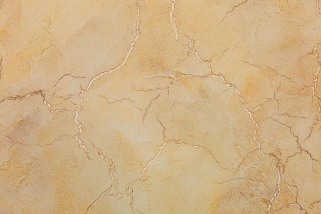 Текстурированный фон желтый трещины штукатурки.