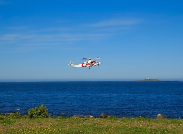 オーレスン、ノルウェーの近くのゴドイ島で海の上のヘリコプター