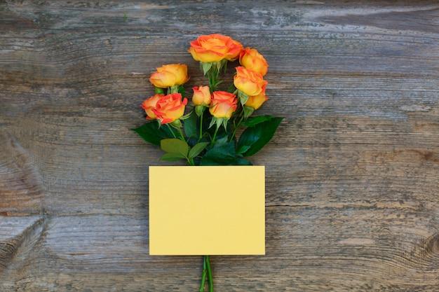 バレンタインまたは母の日に木製の背景にバラと空白のピンクの紙カード
