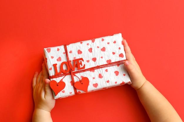 赤の背景に美しいギフトボックスを保持している子供の手