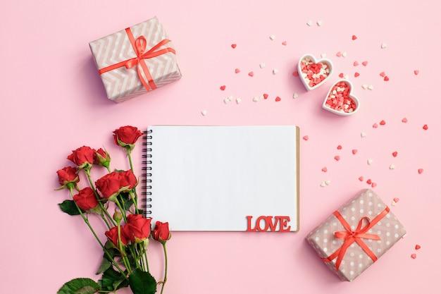 ギフト用の箱、花、ピンクの背景にハートの空白のノートブックを開く