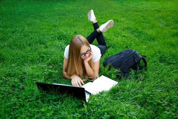 Молодая девушка лежит на траве в парке