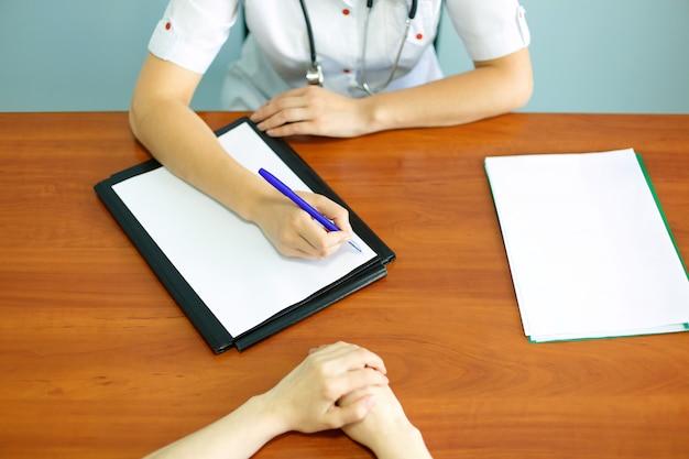 患者と医師がメモを取ってのクローズアップ