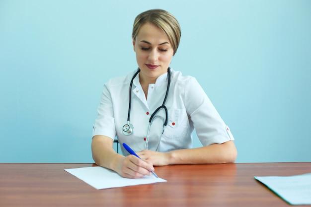 聴診器で自信を持って女性医師がテーブルに座っているし、推奨事項を書き出し