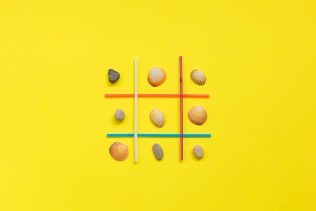 黄色の背景に貝殻と海の石の間の選択競争ゲーム