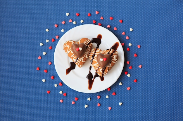 青色の背景に小さな白い皿の上のハートの形のクッキー