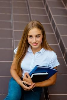 建物の外に立っている女子大学生の肖像画