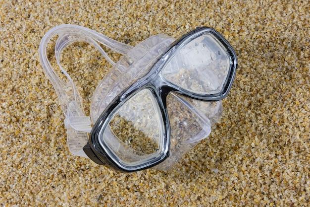 ビーチの砂の上にウェットダイビングマスク。夏のスポーツとレジャー。
