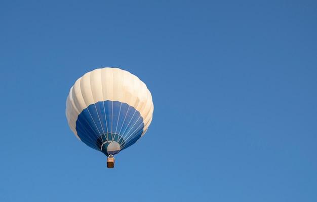 青い空を飛んでいる青と白の熱気球