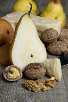 Различные сладкие груши на старый деревянный стол и орех