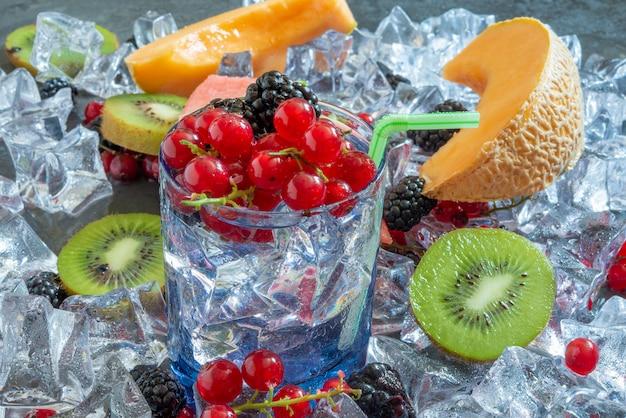 Стакан утоления жажды с холодной водой и свежие летние фрукты со льдом