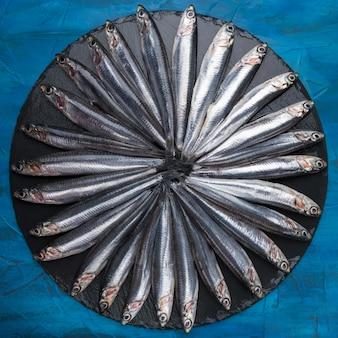 黒い石の上に円の形をしたアンチョビ。シーフード。小さな海の魚