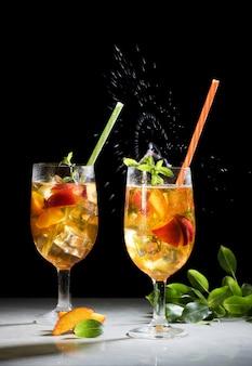 桃の氷の夏のカクテルやお茶、美しいスプラッシュと桃のサングリア