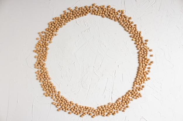 生ひよこ豆、明るい背景にひよこ豆のラウンドフレーム