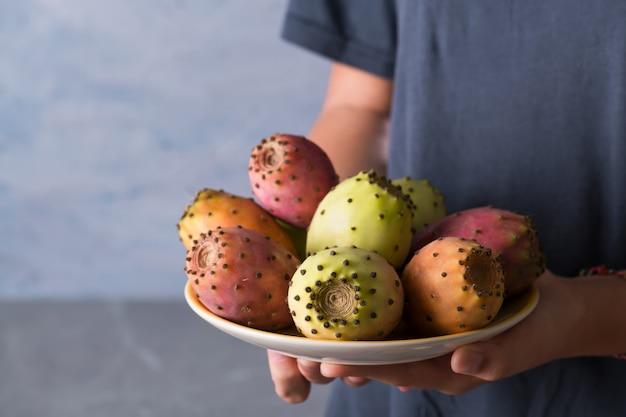 女性の手は、灰色の背景にウチワサボテンの熟した新鮮なフルーツプレートを保持します。