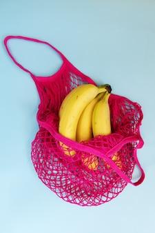 Три желтых спелых банана в сумке из фуксии