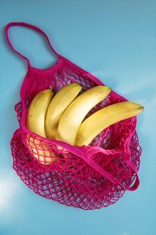 メッシュストリングバッグ入りのオーガニックバナナ。フラット横たわっていた、トップビュー。廃棄物ゼロ、プラスチックフリーのコンセプト。健康的な清潔な食事とデトックス