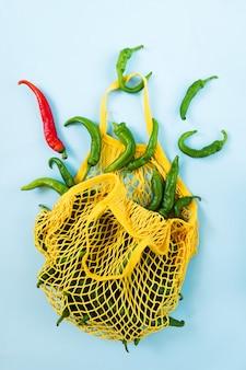 創造的なレイアウト緑唐辛子。黄色のひもの袋に入れた緑の野菜。フリギテリと呼ばれるピーマンの山
