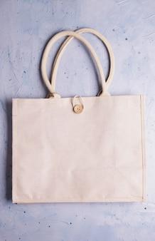 Экологичная многоразовая хлопчатобумажная экологическая сумка на сером. ноль отходов