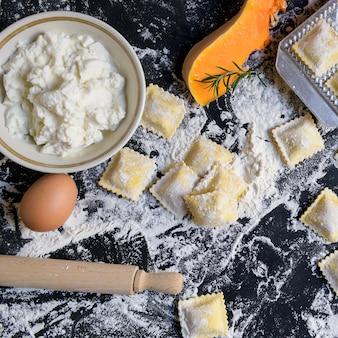 小麦粉、手作り、調理プロセスの木製テーブルの上のカボチャと伝統的な生ラビオリ
