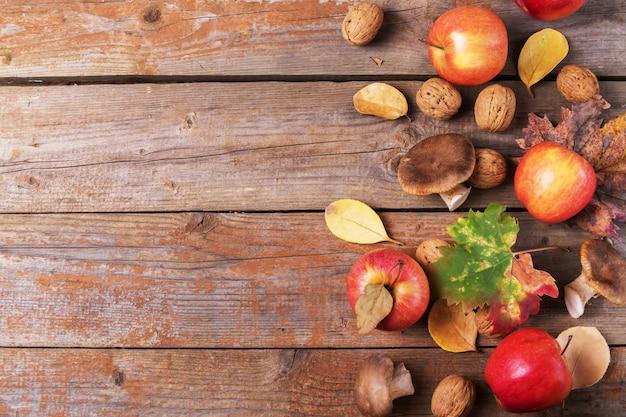 Картофельные грибы, яблоки, грецкие орехи и разноцветные листья на старых деревенских деревянных досках. осенний день благодарения фон