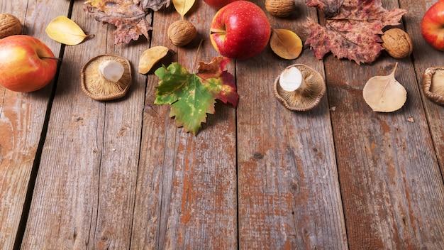 Картофельные грибы, яблоки, грецкие орехи и разноцветные листья на старых деревенских деревянных досках. осенний день благодарения фон, копия пространства
