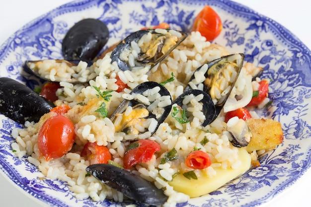 米、じゃがいも、ムール貝、伝統的なプルーン料理、イタリア料理、バーリ、青のプレートの上にクローズアップ