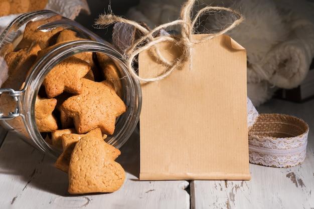 木製のテーブルにハートの形をしたジンジャークッキーとクラフト紙のメモまたはグリーティングカード。