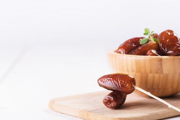 木製のボウルに生の甘い乾燥ナツメヤシ