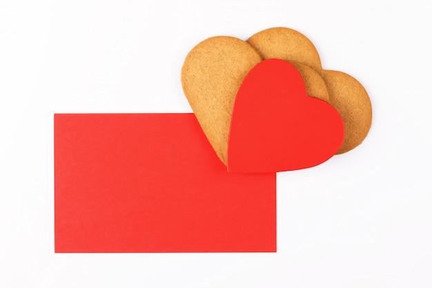 白地にハート形のクッキーと赤いグリーティングカード。居心地の良い愛とバレンタインデーの背景のシンボル