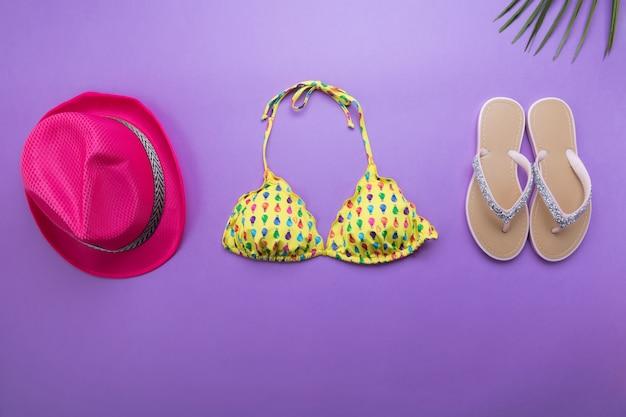 ヤシの葉、ピンクのファッション帽子、紫または紫の表面、旅行や休暇の概念、トップビューでビキニ