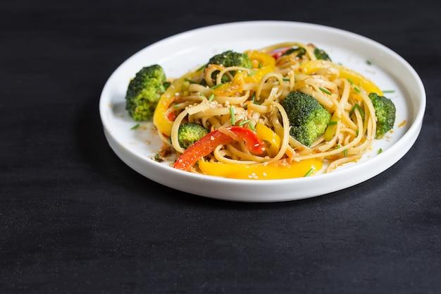黒の背景に野菜とうどん、鍋で炒め炒め
