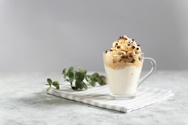 チョコレートの滴で透明なガラスのコップにダルゴナの泡だらけのコーヒー、牛乳と灰色の壁にコーヒーの泡で作られたトレンド韓国ドリンク