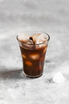 Замороженный черный заварной кофе в высоком стакане с кусочками льда на серой темной стене, крупный план