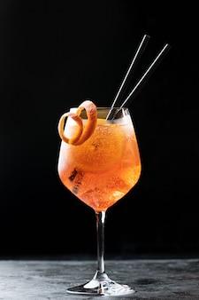 黒のガラスの古典的なイタリアのアペロールスプリッツカクテルをクローズアップ