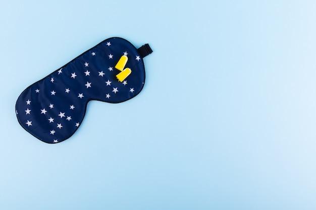 Синяя маска для сна и затычки для ушей на синем фоне