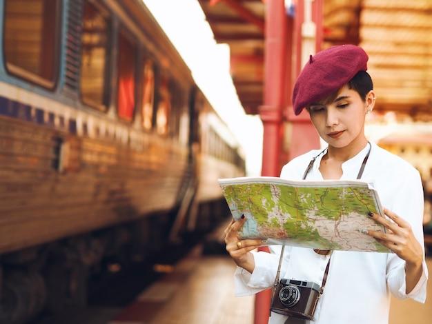 地図、旅行コンセプトを保持する若いアジアの女性